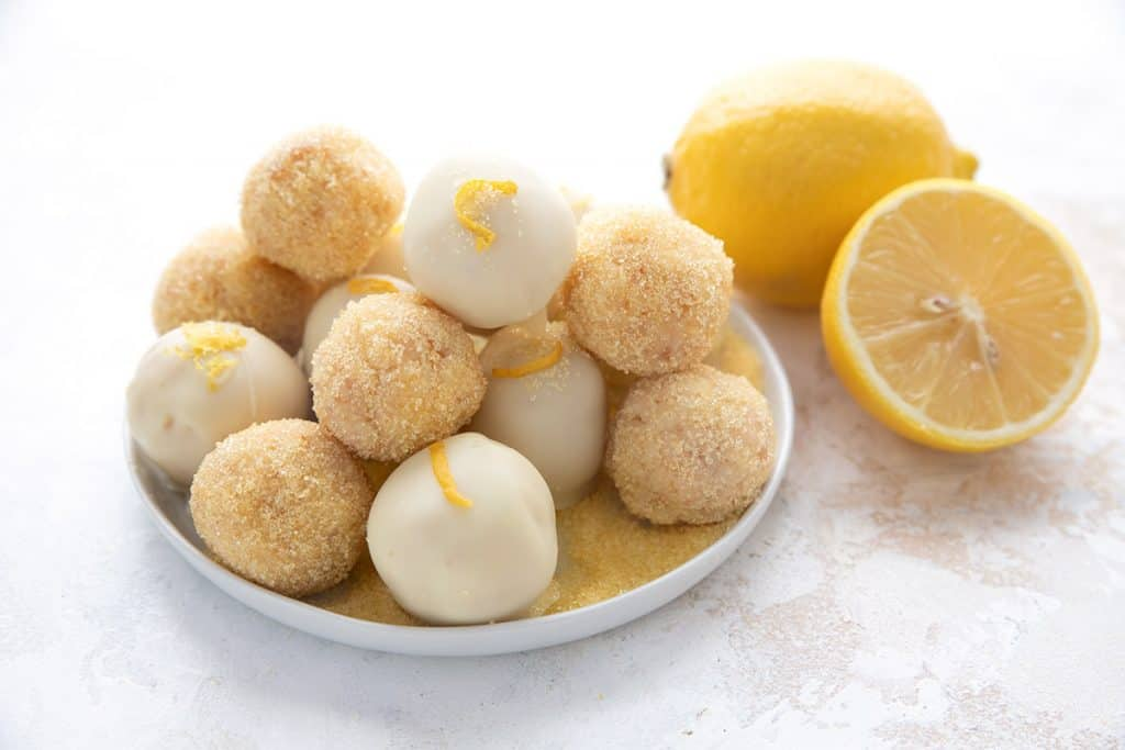 Lemon cake balls on a white plate with a lemon and a lemon half beside them.