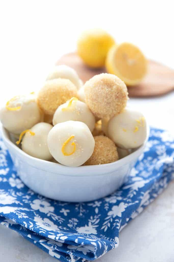 A bowl of keto lemon truffles on a blue napkin, with lemons in the background