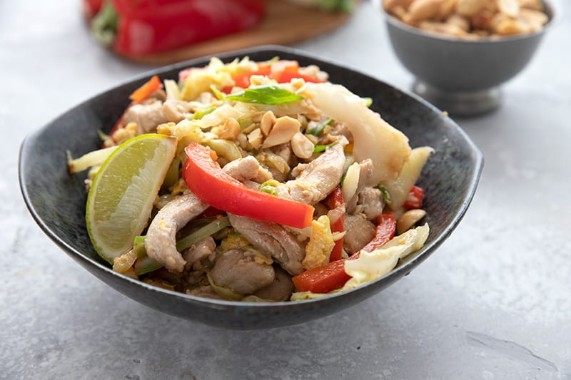A black bowl filled with keto pad thai, garnished with peanuts and a slice of lime.