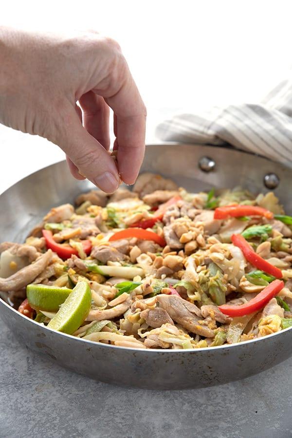 A hand adding peanuts to a skillet full of keto pad thai