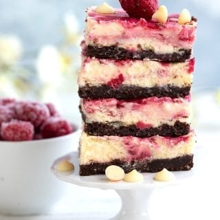 A stack of keto raspberry cheesecake bars on a cake stand, with raspberries in the background