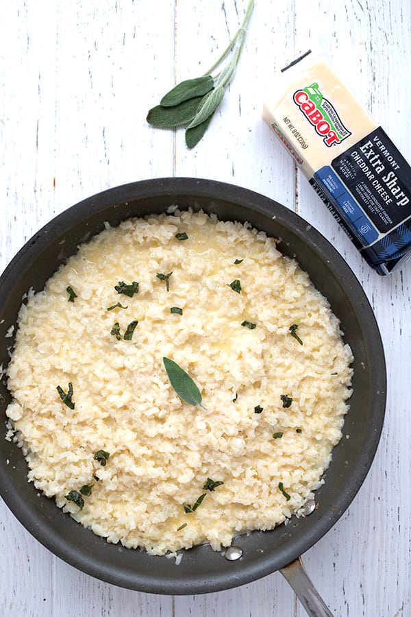 A pan of cheesy cauliflower risotto on a white table with a block of cheddar and some sage leaves.