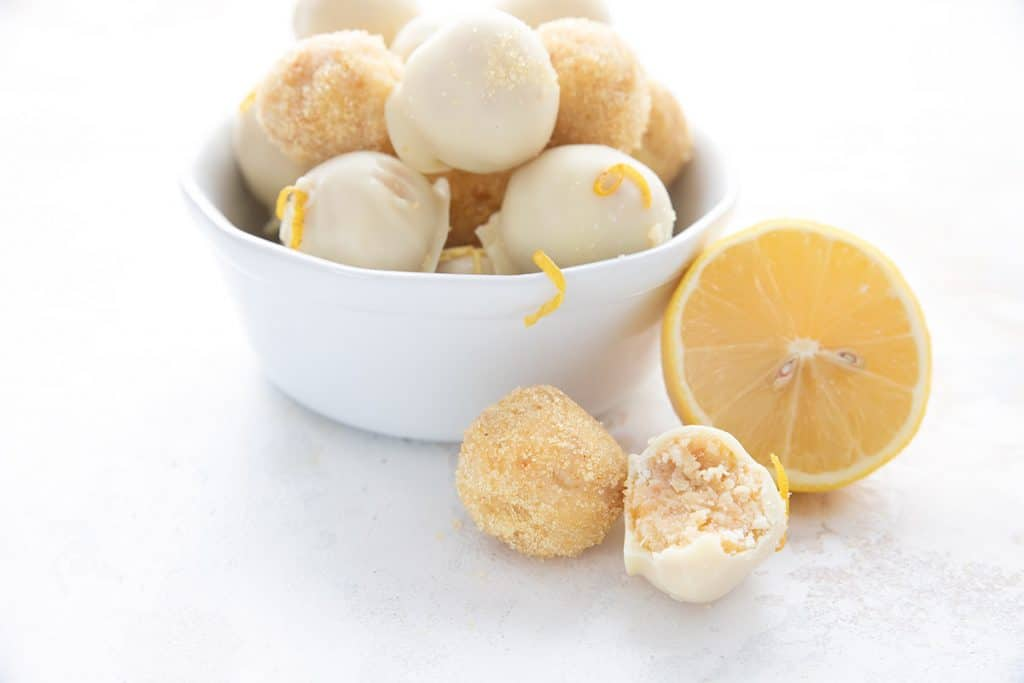 Two keto lemon cake balls in front of a bowl of more truffles, with a lemon half beside the bowl.