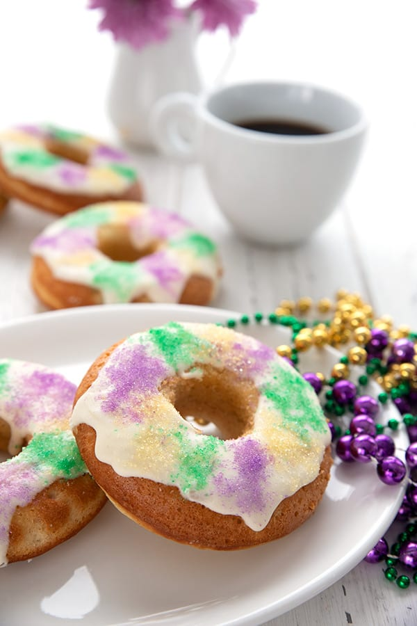 A keto king cake donuts sits on a white plate, with Mardi gras beads off to the side. A cup of coffee and more donuts in the background.