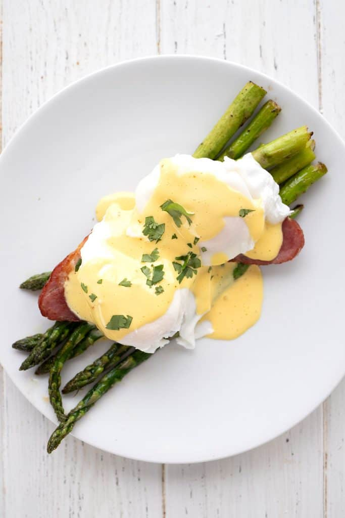 Top down image of poached eggs and hollandaise sauce over asparagus on a white plate.