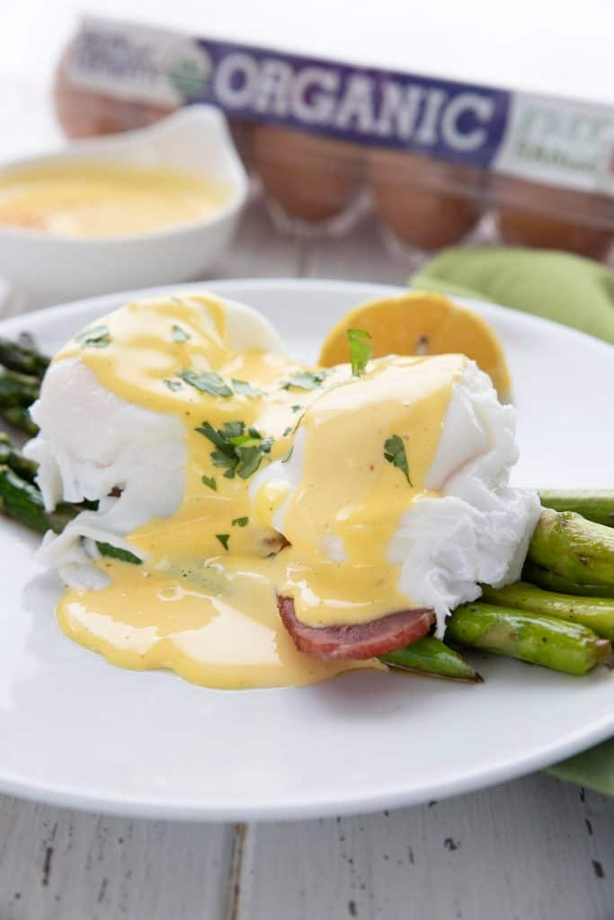Keto asparagus Benedict on a white plate with a carton of eggs in the background.