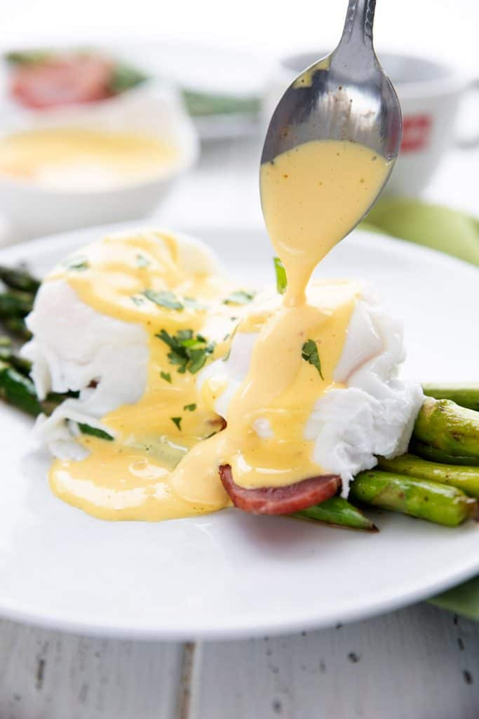 Freshly made hollandaise sauce pouring off a spoon onto poached eggs.