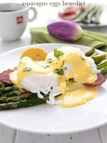 Titled image of eggs benedict served over asparagus on a white plate. A cup of coffee and a purple tulip in the background.
