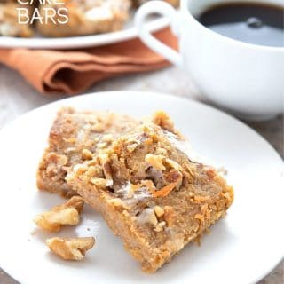 Titled image of two keto carrot cake bars on a white plate with a cup of coffee in the background.