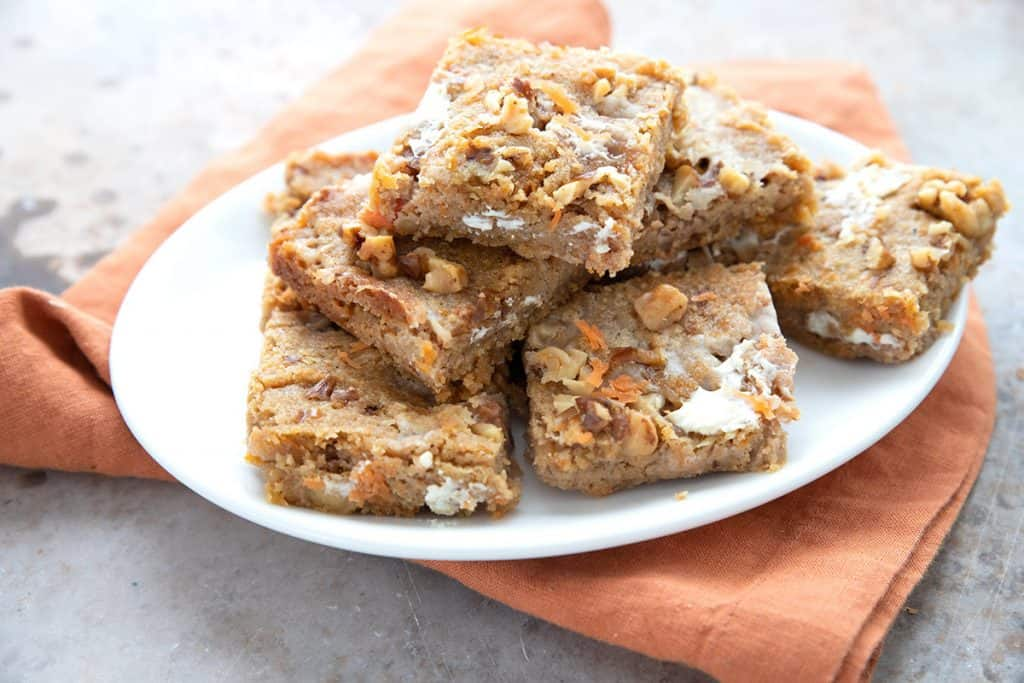 A plate of sugar free keto carrot cake bars over an orange napkin.