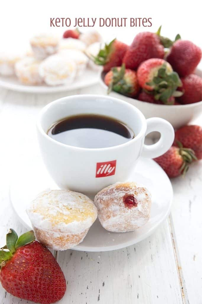 Titled image of keto jelly donut muffins on a saucer with a cup of coffee and strawberries in the background.