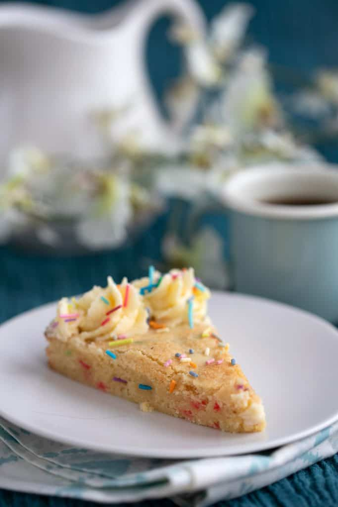 A slice of sugar cookie cake on a white plate with a cup of coffee in the background.