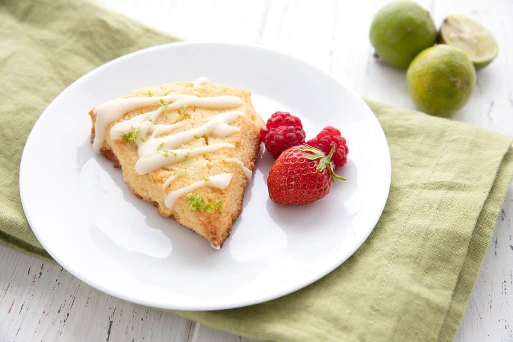 A key lime scone on a white plate with some berries, over a green napkin.