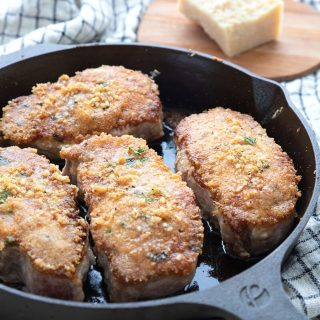 Title image of parmesan crusted pork chops in a cast iron skillet over a plaid napkin