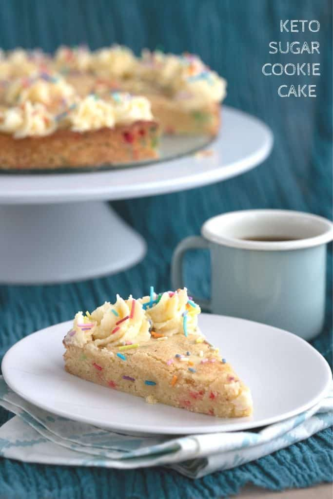 Titled image: a slice of keto sugar cookie cake on a white plate, with the rest of the cake in the background on a cake stand.