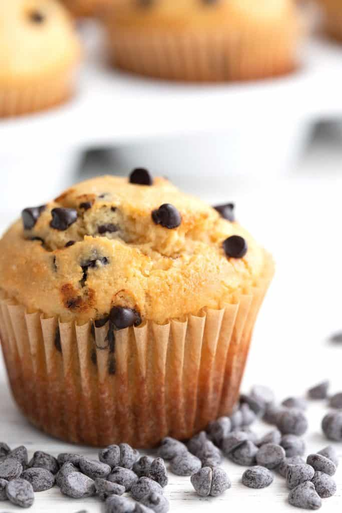 Close up shot of a bakery style keto muffin with chocolate chips all around it.