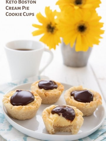Titled image of Boston Cream Cookie Cups on a white plate over a blue patterned napkin, with a vase of yellow flowers and a cup of coffee in the background.