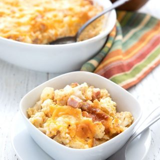Titled image of keto ham and cauliflower casserole in a small dish, in front of the larger casserole