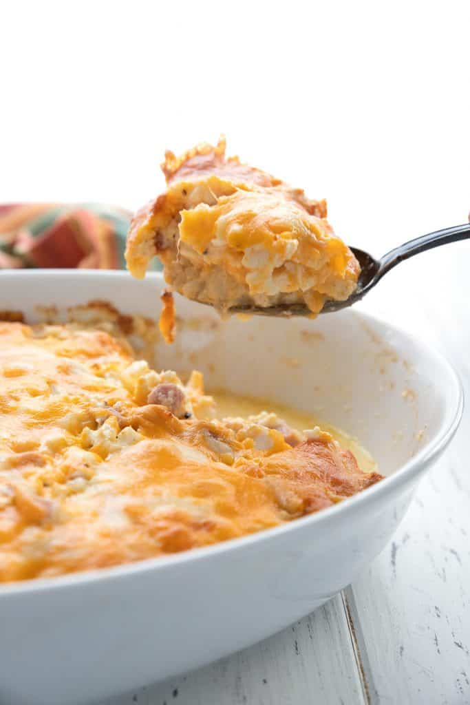 A spoonful of ham and cauliflower casserole being lifted out of the casserole dish.