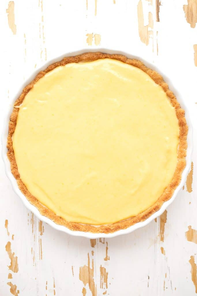 Top down image of keto lemon curd tart in a white ceramic tart pan on a weathered white table.