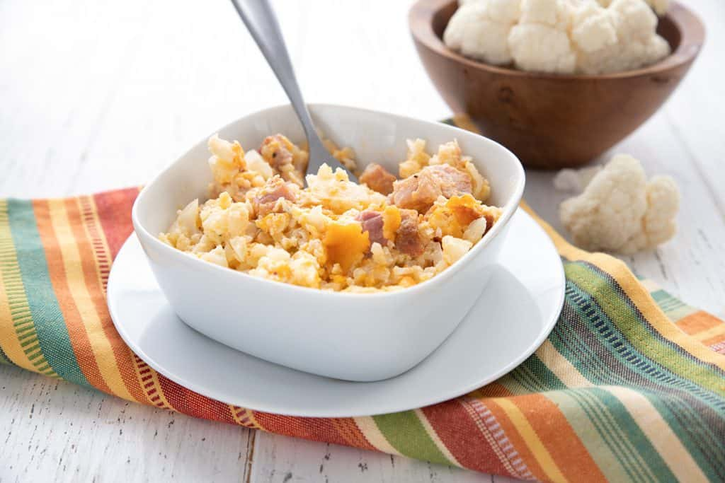 A serving of keto ham and cauliflower casserole in a small white dish.