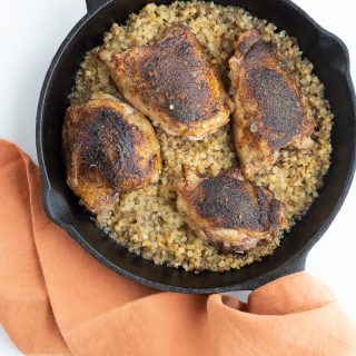 Top down image of keto jerk chicken and rice in a cast iron skillet, with an orange napkin over the handle.