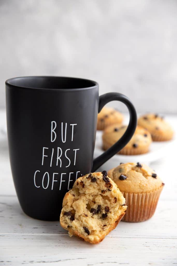 A black coffee mug with a keto chocolate chip muffin broken open, leaning against it