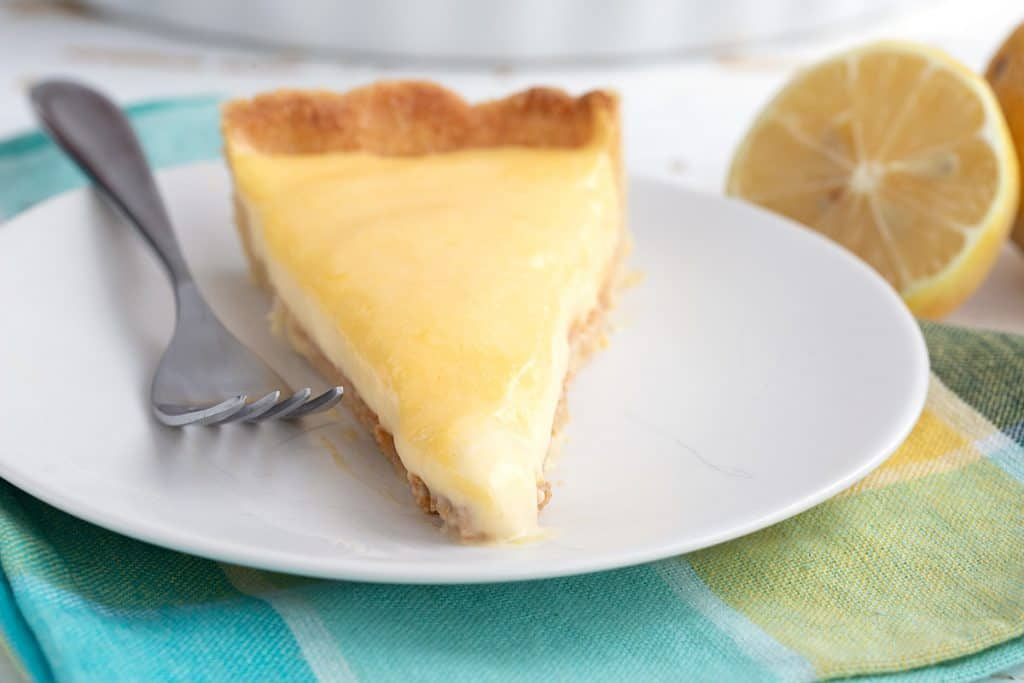 Close up shot of a slice of keto lemon curd tart on a colourful yellow and teal napkin.