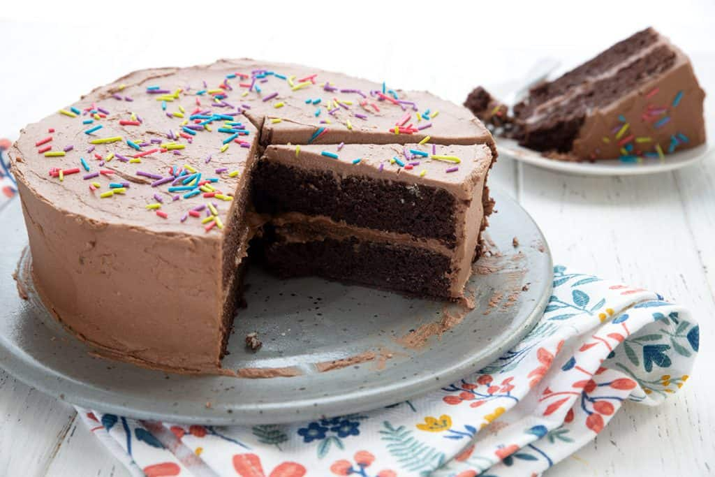 Keto chocolate mayonnaise cake on a large grey cake plate over a colorful patterned napkin, with a slice cut out of it.