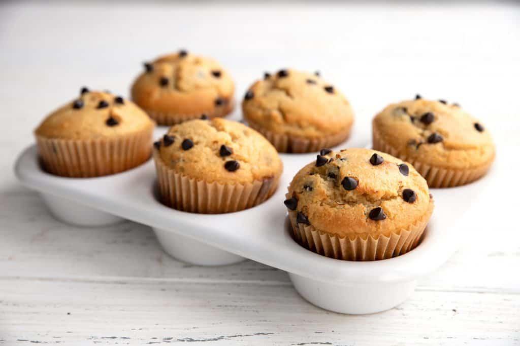 6 keto chocolate chip muffins in a white ceramic muffin pan.