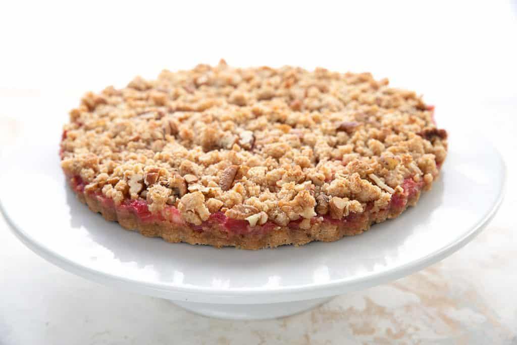 Keto rhubarb crumple tart sits on a white cake stand.