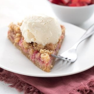 A slice of keto rhubarb crumble tart on a white plate with a scoop of sugar-free vanilla ice cream.