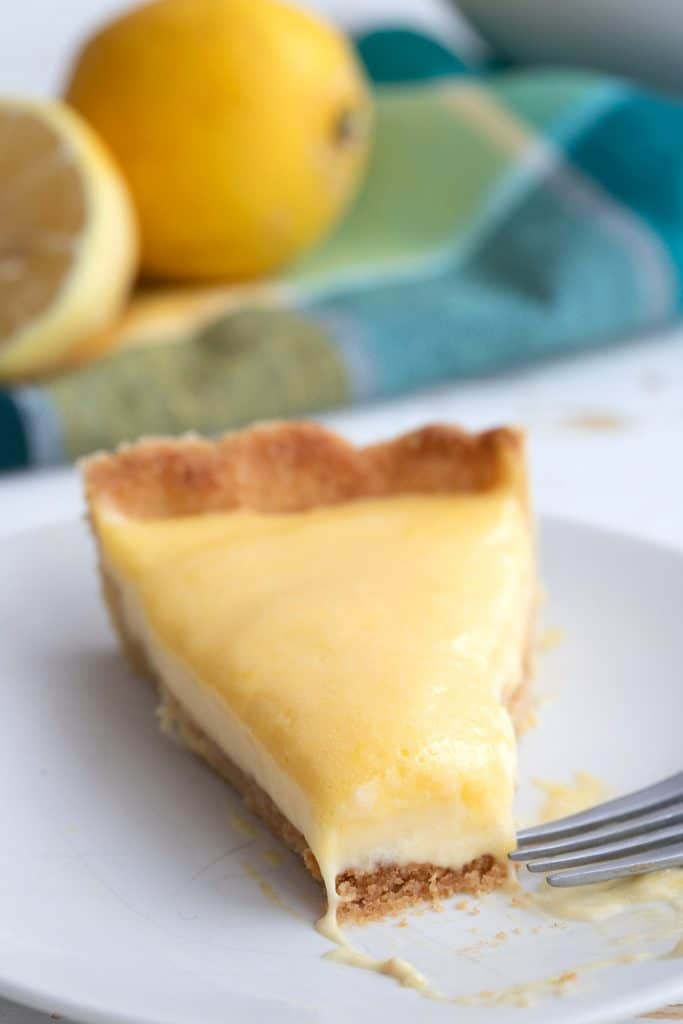 Close up shot of a slice of lemon curd tart with a forkful taken out of it.