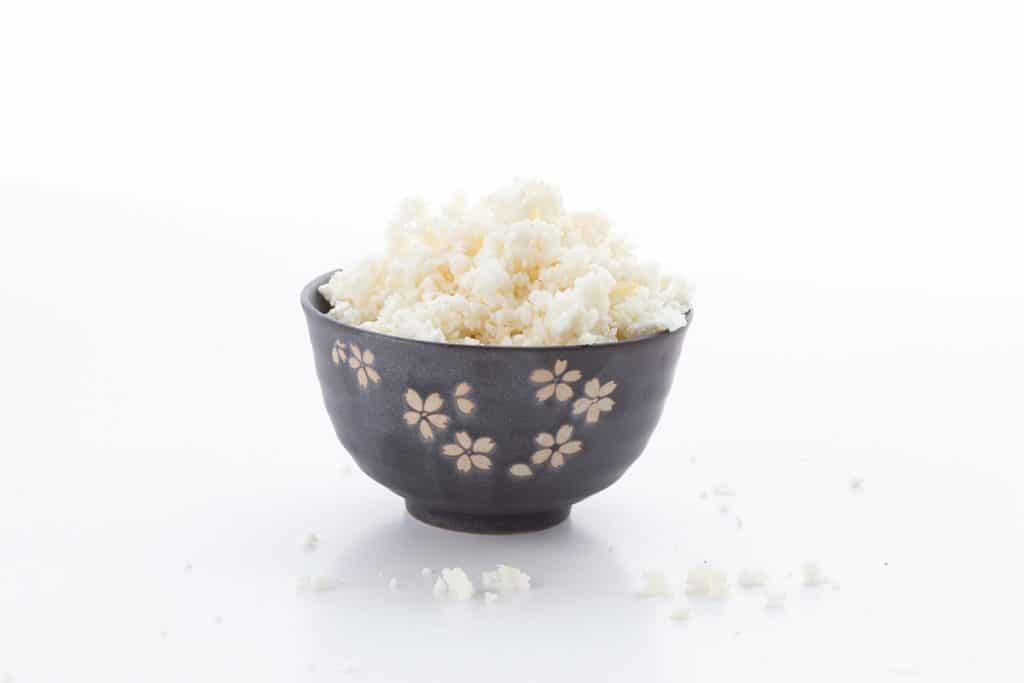 A black bowl filled with riced cauliflower.