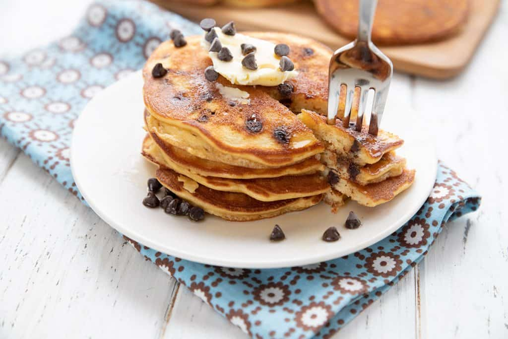 A stack of banana chocolate chip pancakes with a forkful being taken out.