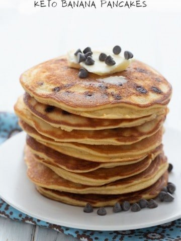 Titled image: A stack of keto banana pancakes on a white plate over a blue patterned napkin, with butter and chocolate chips on top.