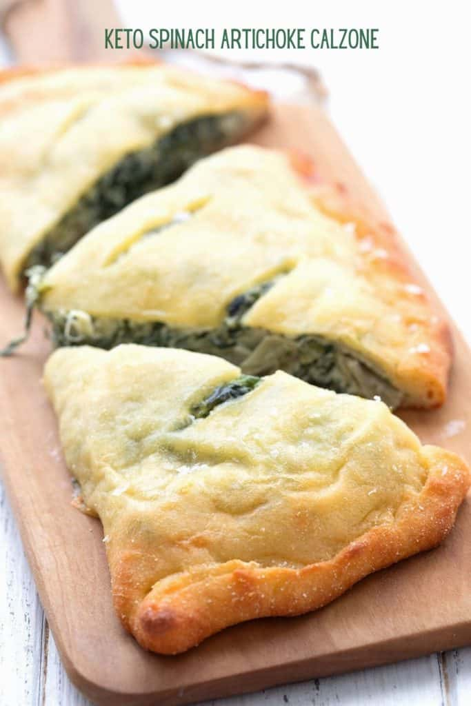 Titled image of a keto spinach artichoke calzone on a cutting board, cut into three pieces.