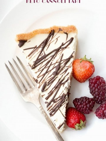 Top down image of a slice of keto cannoli tart with berries on the side, on a white plate.