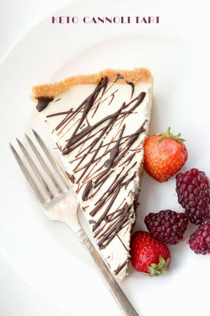 Top down image of a slice of keto cannoli tart on a white plate with fresh berries.