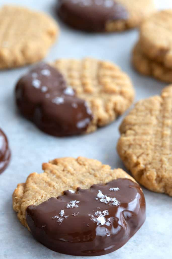 Close up shot of chocolate dipped peanut butter cookies sprinkled with sea salt.