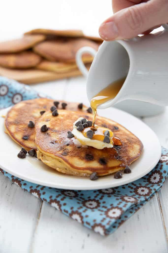 Sugar free syrup being poured out of a small white pitcher onto a plate of keto banana pancakes.