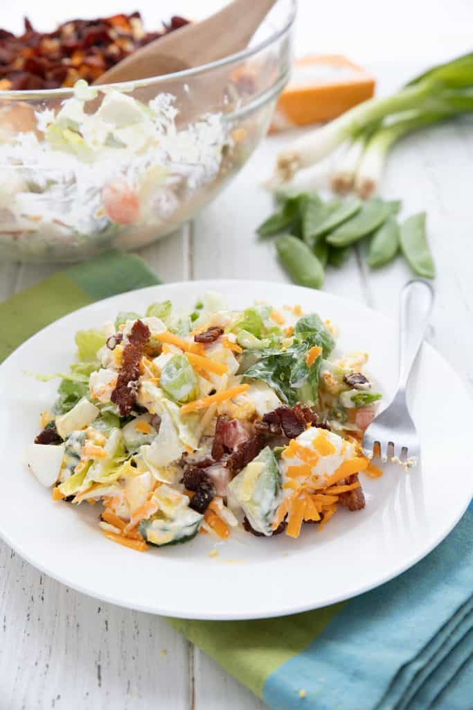 A plate filled with keto seven layer salad, with the bowl in the background and some of the ingredients in behind.