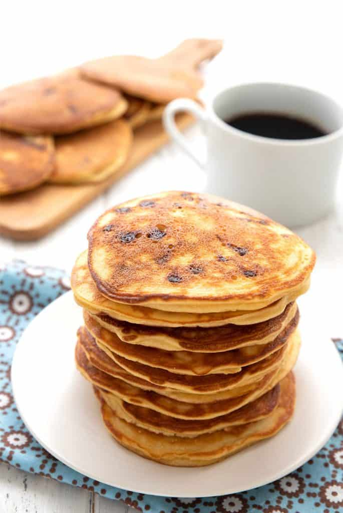 A large stack of keto banana pancakes on a white plate with a cup of coffee in the background.