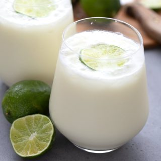 Two glasses filled with keto limeade on a grey concrete table with limes in the background.