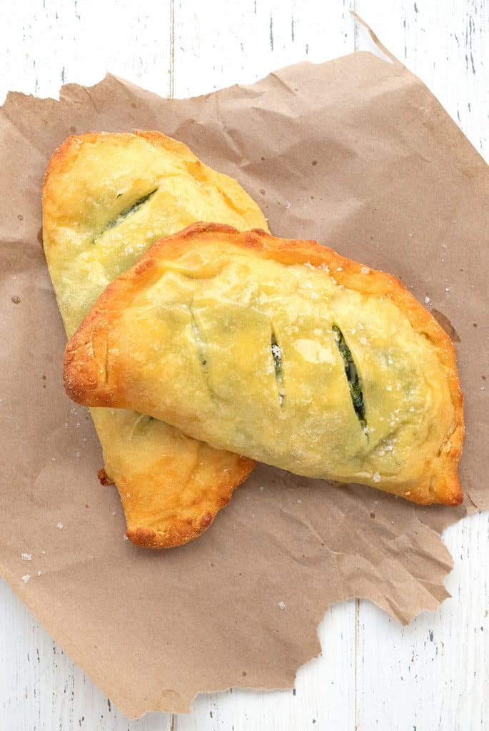 Top down image of keto calzones on a piece of brown paper over a white table.