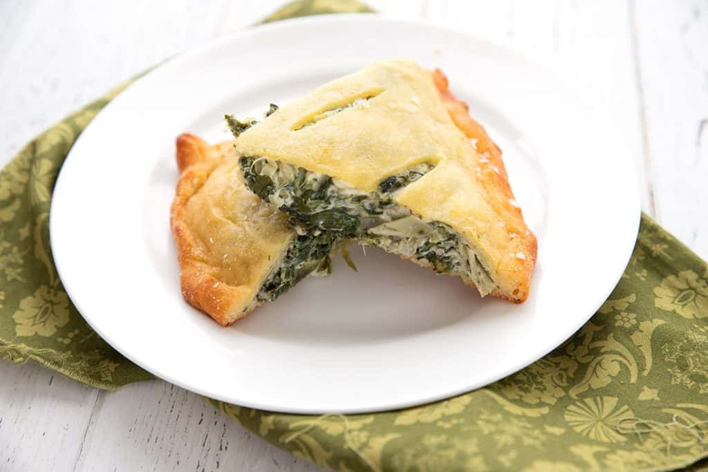 Two slices of keto spinach calzone on a white plate over a green patterned napkin.