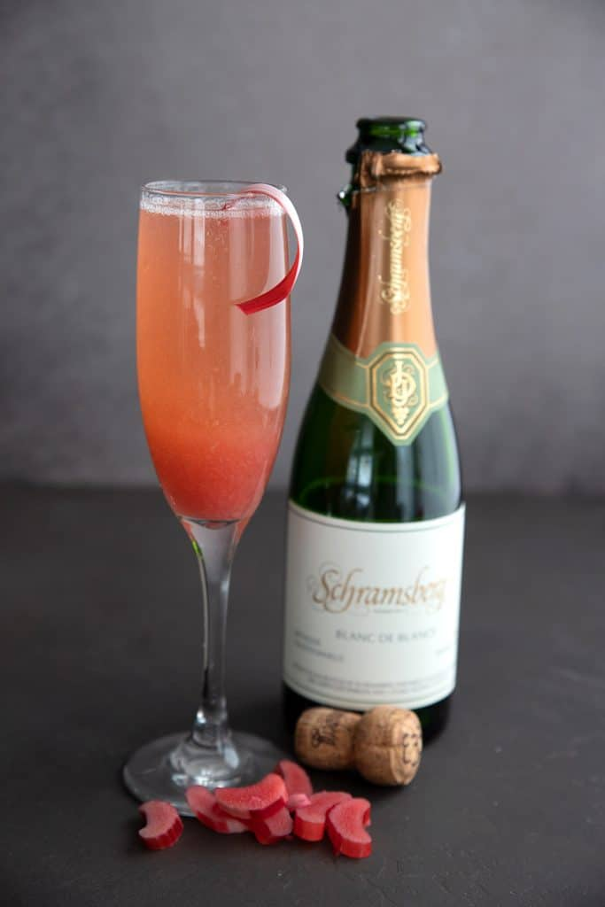 A sugar free rhubarb cocktail in a champagne flute sits beside a bottle of champagne with sliced rhubarb all around the bottom.
