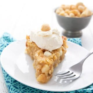 A slice of Keto White Chocolate Macadamia Nut Pie on a white plate with a bowl of macadamias in the background.
