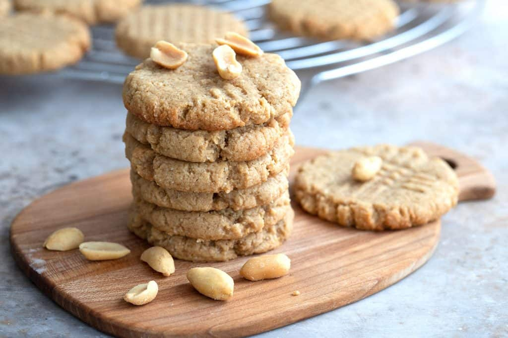 A wooden cutting board with a stack of peanut butter cream cheese cookies on it, and a cooling rack with more cookies in the background.