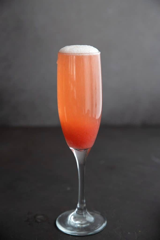 A champagne flute filled to the brim with sugar-free rhubarb fizz cocktail in a dark background.